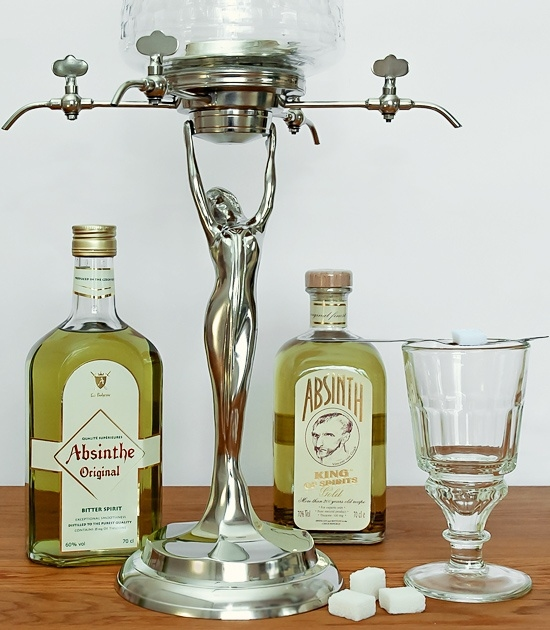 Traditional absinthe glass Pontarlier with two bottles of premium absinthe and Lady Absinthe Fountain.