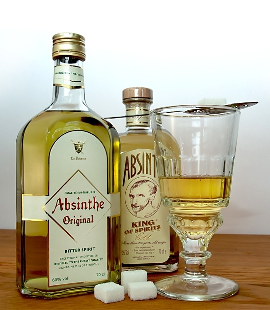 Pontarlier absinthe glass with absinthe drink, spoon, sugar cubes abd bottles of premium absinthe liquor.