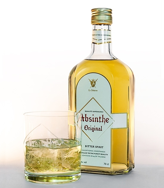 Heavy based short tumbler absinthe glass with absinthe on ice and bottle of Real Absinthe Original Bitter Spirit