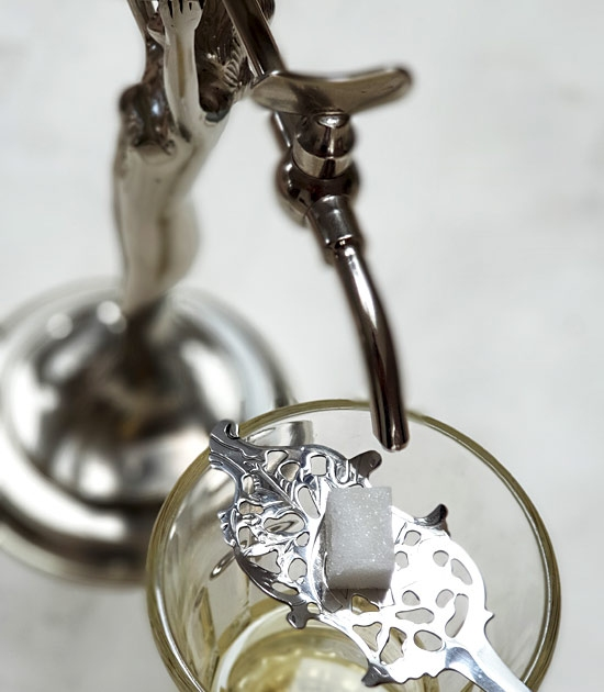 Metal tap (spigot) and detail of absinthe wormwood spoon sitting on an absinthe glass.