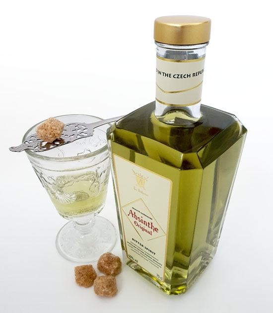 Bottle of absinthe with absinthe glass, slotted absinthe spoon and sugar.