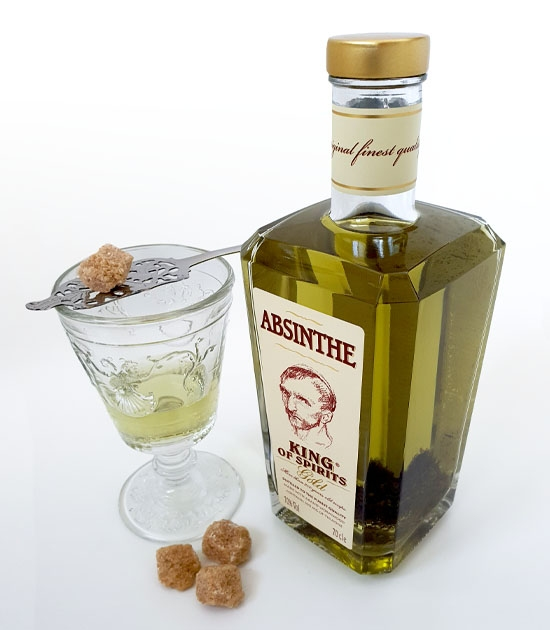 Bottle of King Gold Absinthe with absinthe drink, Versailles absinthe glass, silver spoon and sugar.
