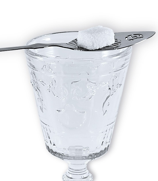 Detailed image of absinthe spoon on the rim of the glass with a cube of sugar set on top
